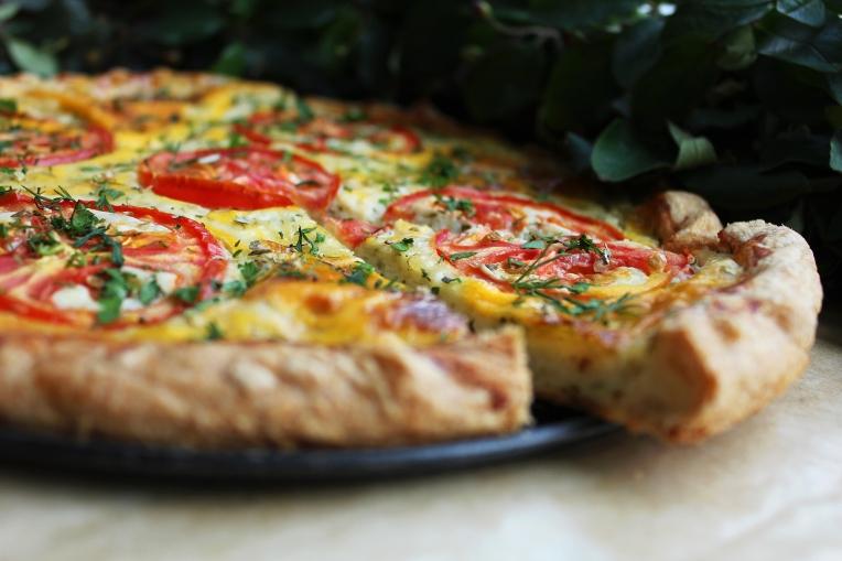Doe 350 g pizzamix in een grote beslagkom, maak een kuiltje in het midden en schenk hier het lauwwarme water en de olijfolie in. Roer van het midden uit steeds meer bloem door het vocht, blijf roeren tot alles is vermengd. Kneed dan alles tot een soepel deeg. Dit kan zowel met de hand als met een mixer met kneedhaken of een keukenmachine.